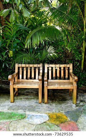 Two wooden chairs in a garden with tropical leaves in the background. - stock photo