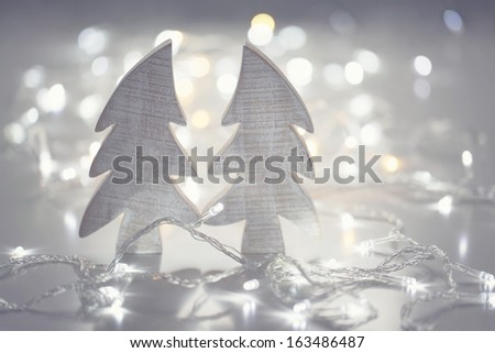 Two wooden christmas fir trees with led lights on shiny background - stock photo