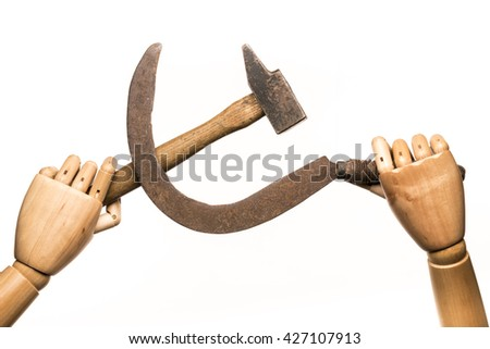 Two wooden hands brandishing a rusty sickle and a used hammer. On white background. With copy-space. - stock photo