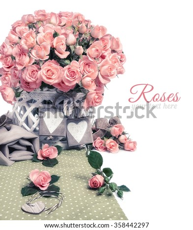 Two wooden heart tags among pink roses, isolated on white. Text space on the right. Corner element for design for a special occasion: Anniversary, Mothers day or St. Valentine. This image is toned. - stock photo