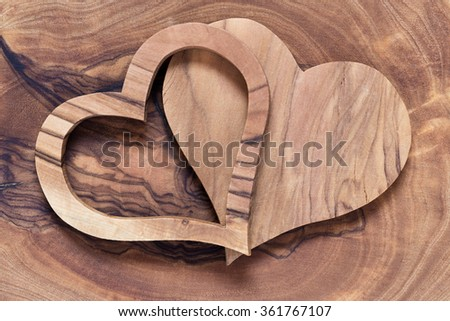 two wooden hearts on a wooden background, olive wood, copyspace, horicontal, concept wedding - stock photo