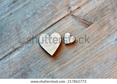 Two Wooden Hearts on Wooden Background as seen from Above - stock photo