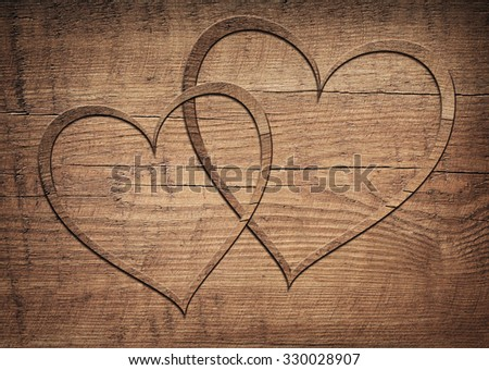 Two wooden hearts placed on a brown wood board - stock photo