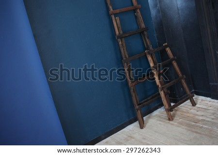 Two Wooden ladder, near dark blue wall, perspective     - stock photo