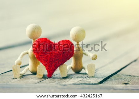 Two wooden little men with heart. Love concept or valentines card - stock photo