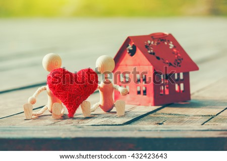 Two wooden little men with heart near house - stock photo