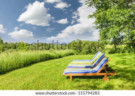 Two wooden outdoor lounge chairs on lush green lawn with trees - stock photo