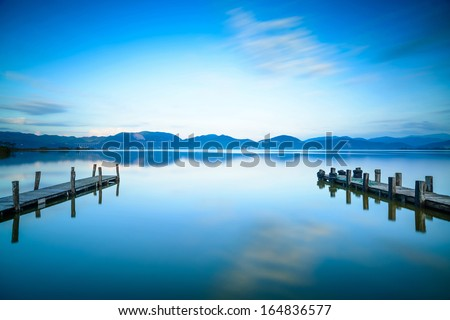 Two Wooden pier or jetty on a blue lake sunset and cloudy sky reflection on water. Long exposure, Versilia Massaciuccoli Lake, Tuscany, Italy. - stock photo