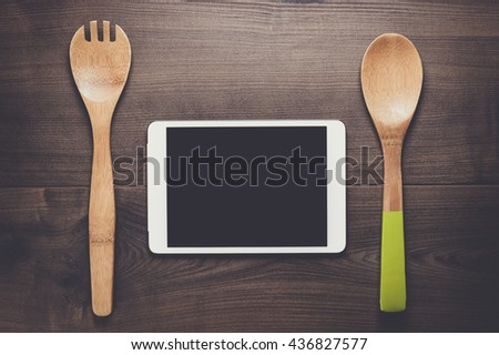 two wooden spoons and tablet computer on the brown table - stock photo
