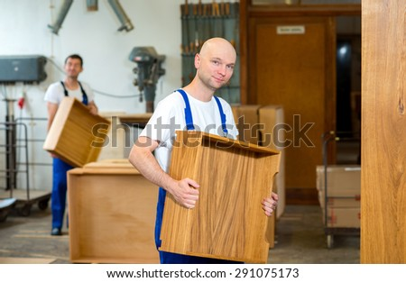 two worker in blue dungarees in a carpenter's workshop - stock photo