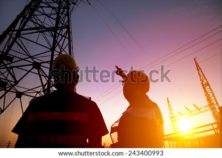 two worker watching the power tower and substation with sunset background - stock photo