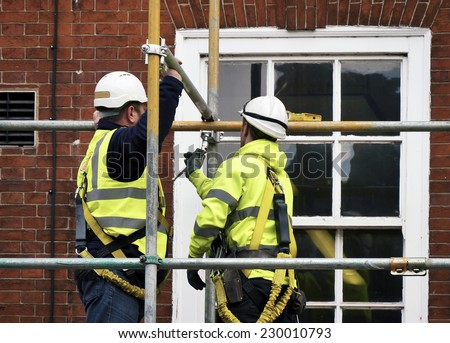 Two workers assembling scaffolding on city building - stock photo