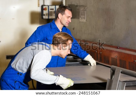 Two workers bending sheet metal with a large machine - stock photo