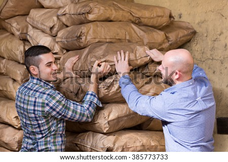 Two workers carrying bags of cement at the construction site  - stock photo