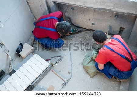 Two workers have made a niche for radiators in apartment - stock photo