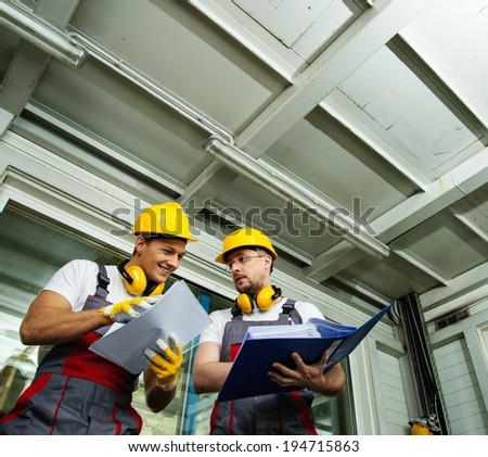 Two workers  in a factory control room reading documentation  - stock photo
