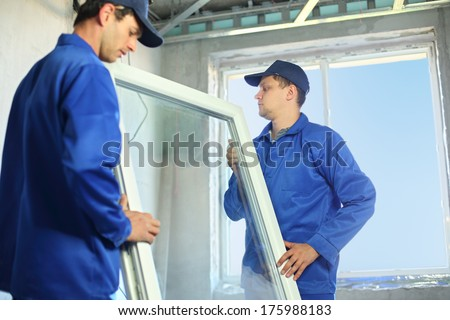 Two workers in blue work clothes set a new window in the window frame - stock photo