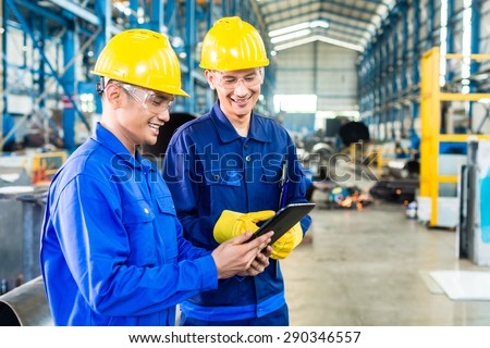 Two workers in production plant as team discussing, industrial scene in background - stock photo