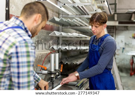 Two workers near milling machine at factory - stock photo