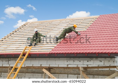 two workers on roof at works with metal tile and roofing iron - stock photo