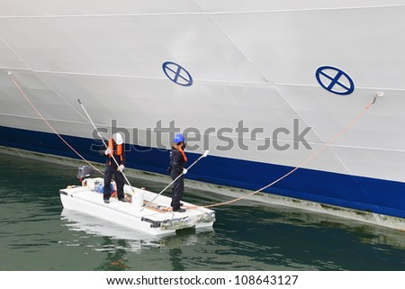 two workers paint board of large cruise liner by white paint - stock photo