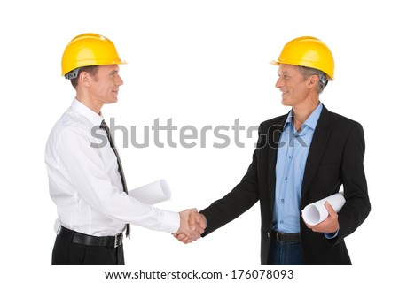 two workers shaking hands and smiling. engineers wearing yellow hardhat and standing - stock photo