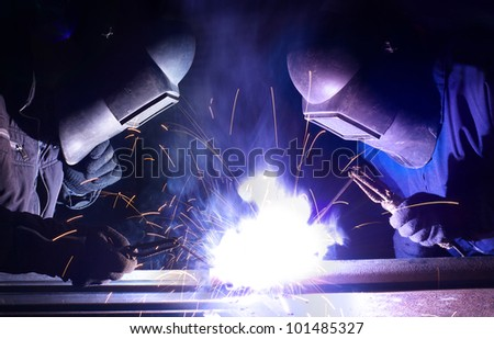 Two workers welds the metal. Construction and production - stock photo
