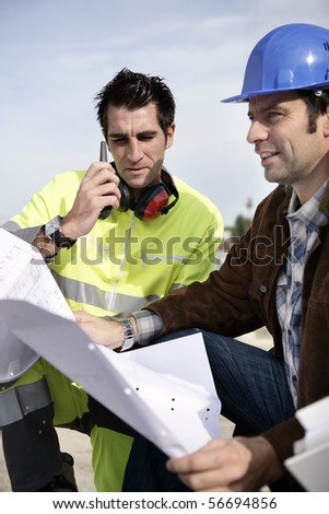 Two workers with a plan and a mobile phone - stock photo