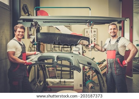 Two workers with car bodykit ready for painting in a workshop - stock photo