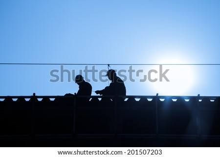 two workers with hardhat working in roof as team - stock photo