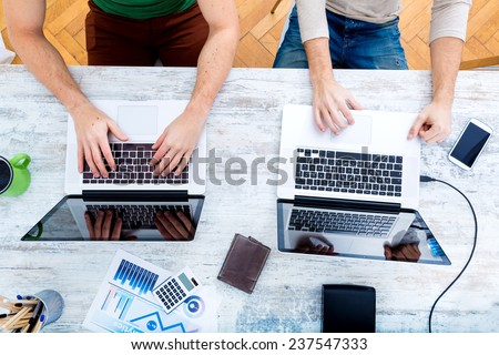 Two workmates teaming up and working together.  - stock photo