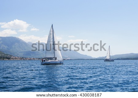 """Two yachts on the water. Tivat, Montenegro - 26 April, 2016. Regatta """"Russian stream"""" in God-Katorskaya bay of the Adriatic Sea off the coast of Montenegro. - stock photo"""