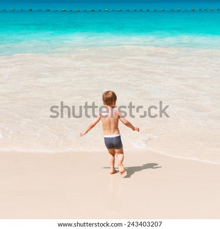Two year old baby boy playing on beach at Seychelles - stock photo