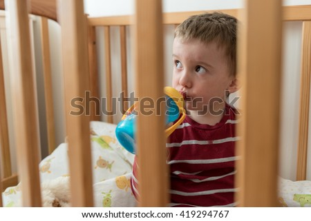 Two year old boy drinking milk from plastic bottle sitting in his bed looking up - stock photo