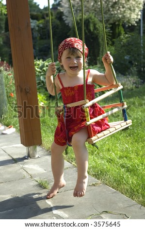 two-year-old girl on a swing in the garden - stock photo