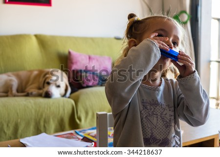 Two year old girl playing harmonica in the living room at home - stock photo