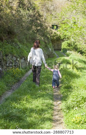 two years age blonde baby with blue dress pigtails and brunette mother woman with grey jersey back walking holding hand in green path in mountain - stock photo