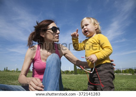 two years aged blonde happy baby yellow shirt talking to brunette woman mother with black sunglasses sitting on green grass lawn - stock photo