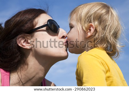 two years old age blonde baby yellow shirt kissing in mouth to brunette woman mother sunglasses with blue sky background - stock photo