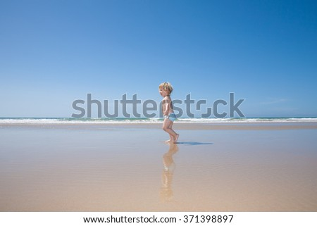 two years old blonde baby with blue swimsuit running on wet sand at sea shore water beach in Cadiz Andalusia Spain - stock photo