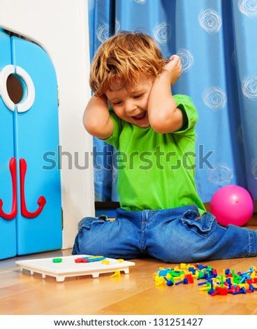 Two years old boy playing and laughing sitting on the floor in his room with mosaic - stock photo