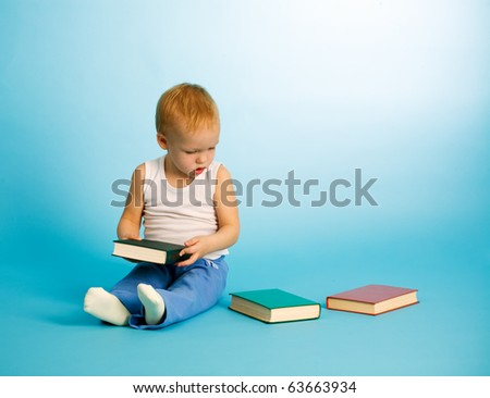 Two years old cute boy chooses what to read from three books. Over blue background - stock photo