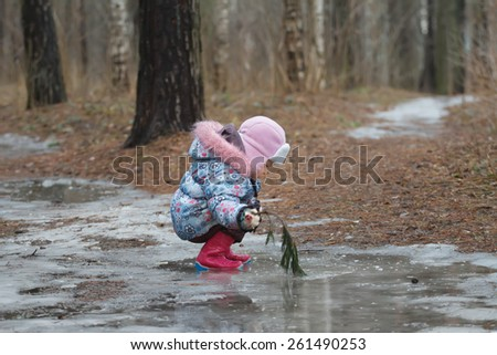 Two years old girl is sitting in icy puddle - stock photo