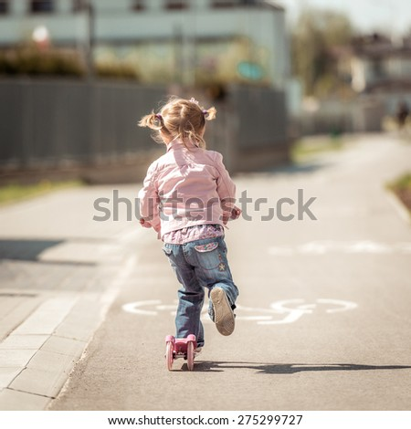 Two years old girl riding her scooter on the street. back  view - stock photo