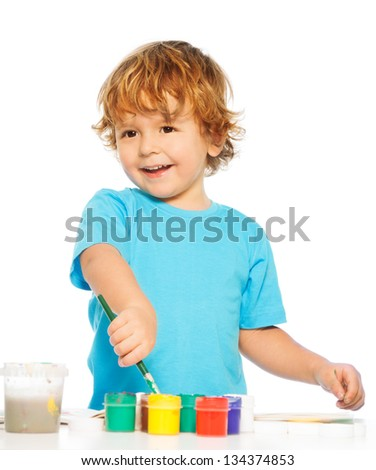 Two years old happy boy painting with paintbrush and colors - stock photo