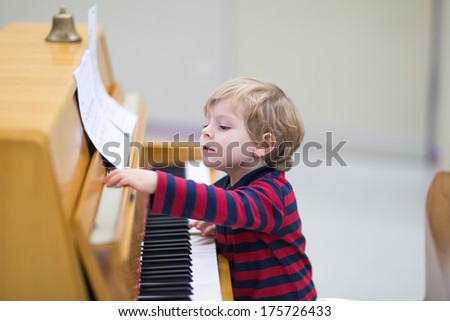 Two years old happy toddler boy playing piano - stock photo