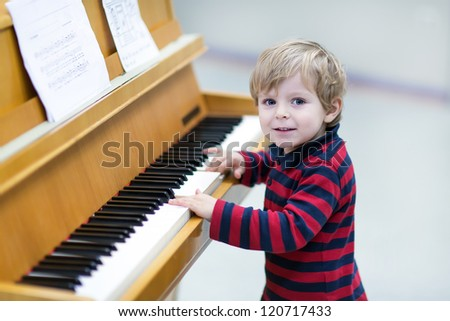 Two years old happy toddler boy playing piano at music school - stock photo