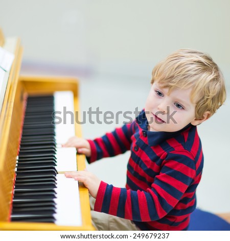 Two years old happy toddler boy playing piano. Early music education for little kids. child at school, learning music instrument. - stock photo