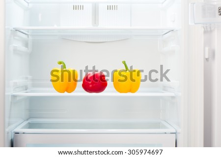 Two yellow and one red peppers on shelf of open empty refrigerator. Weight loss diet concept. - stock photo