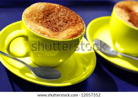 two yellow coffee cups. cappuccino with milk foam  and chocolate powder - stock photo